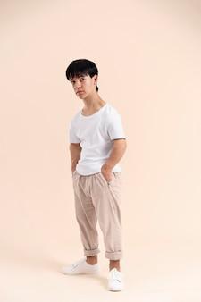 Uomo asiatico in una camicia bianca con posa di nanismo