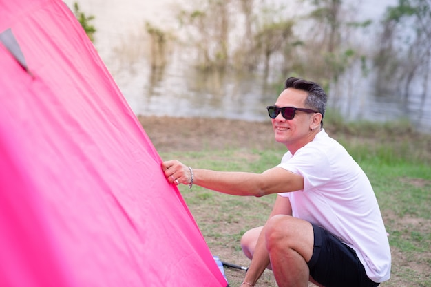 An asian man in white t shirt setting pink tent at campground