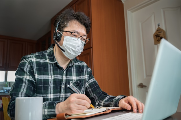 An asian man who is self-isolated and working from home because of a massive pandemic.