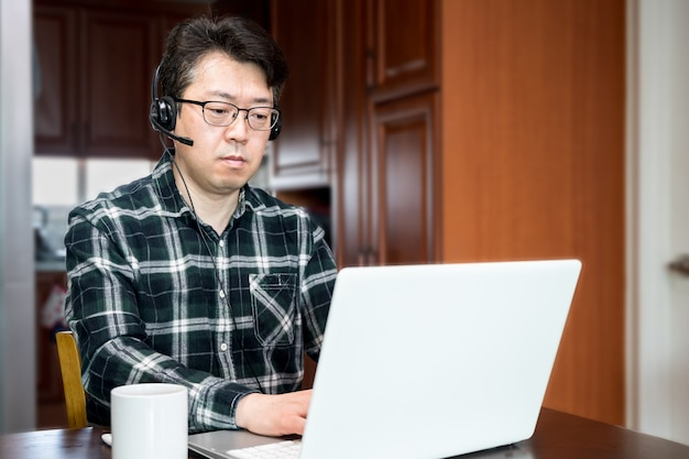 An asian man who is self-isolated and working from home