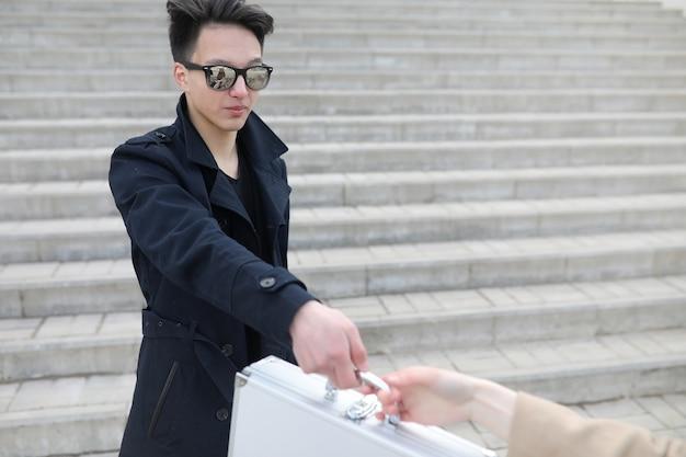 街で金属製のスーツケースを持ったアジア人男性。アジアとシルバーのケース。賄賂用のスーツケースを持ったアジア人。ケースに入った商品でディラー。盗賊の取引。