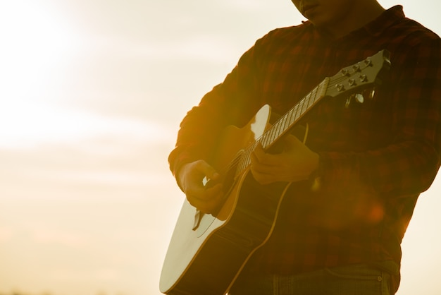 Asian man with acoustic guitar during a sunset