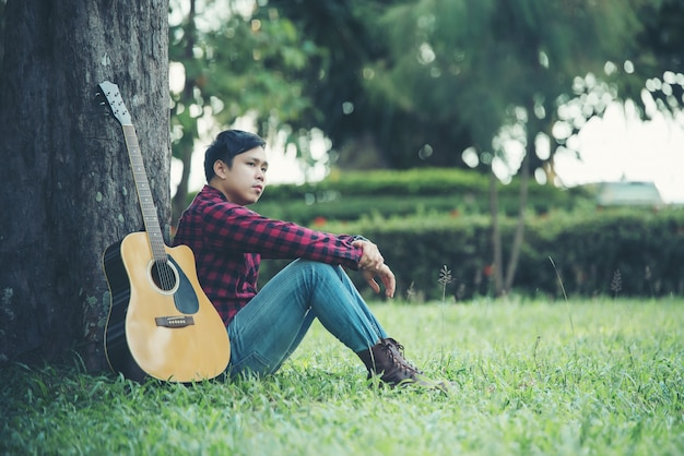 Asian man with acoustic guitar in a park