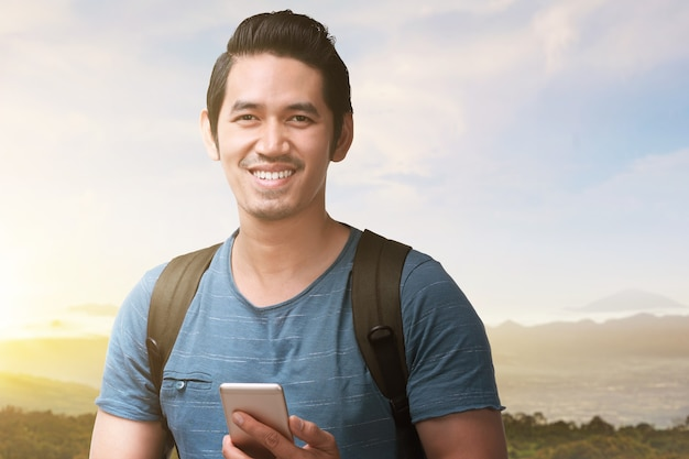 Asian man with a backpack holding smartphone with a landscape view and blue sky. world tourism day