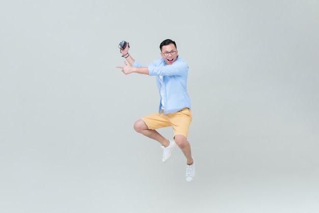Asian man with camera jumping and pointing hand to empty space