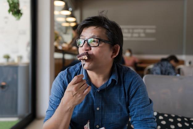 Азиатский мужчина в очках ест шоколадное пирожное в кафе, глядя на улицу, мужчина держит народ с пирожным, кладет в рот