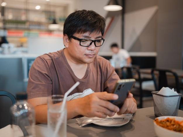 レストランで食事をしている間、スマートフォンで眼鏡を見て、携帯電話中毒、オフィスの外で働いているアジア人男性