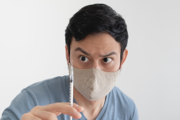 Asian man with a face mask is injecting a vaccine. concept of virus protection.