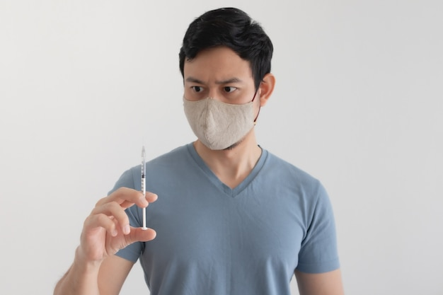 Asian man with a face mask is injecting a vaccine