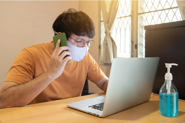携帯電話で話しているカジュアルな服装で眼鏡をかけたアジア人男性、自宅のコンピューターのラップトップ、covid-19コンセプトに取り組んで