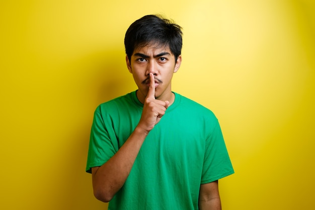 沈黙のジェスチャーをしている孤立した黄色の背景の上に緑のtシャツを持つアジア人男性