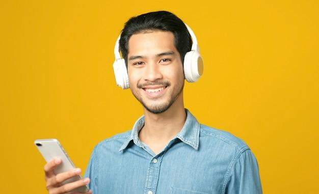 Азиатский мужчина с наушниками, держащий мобильный телефон, смотрит в камеру и улыбается, слушая музыку, изолированные на желтом фоне