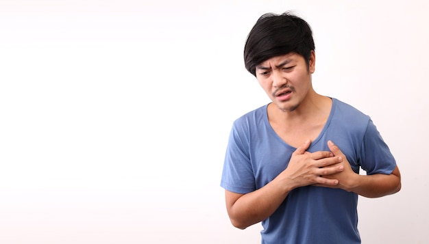 Asian man with heart pain on white background in studio with copy space.