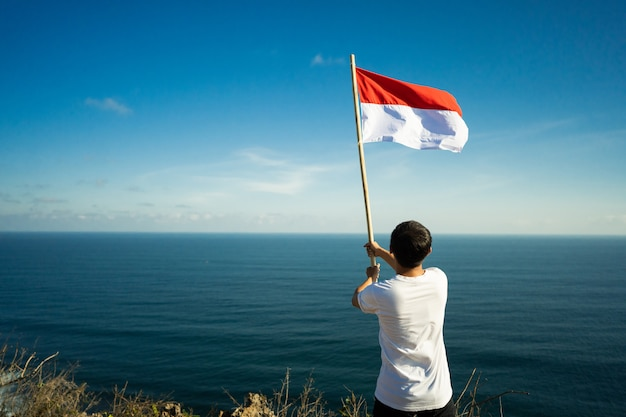 Asian man with indonesian flag of indonesia on top of the mountain