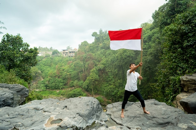 Азиатский мужчина с индонезийским флагом индонезии на вершине горы