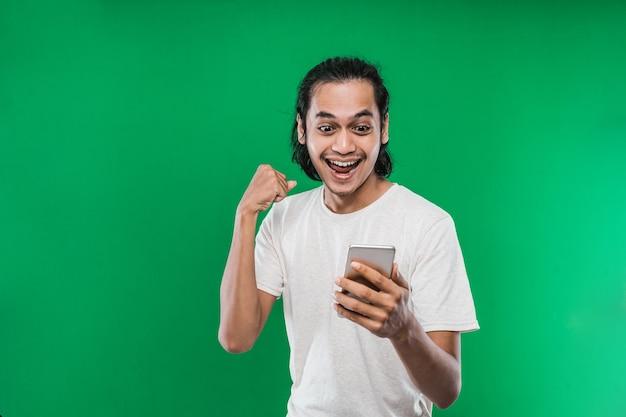 長い黒髪のアジア人男性が片手を上げて拳を作りながら、幸せな表情で携帯電話を見て、緑の背景に分離