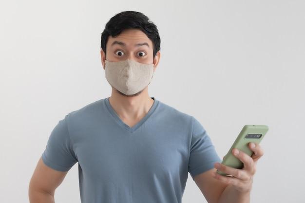 マスクをしたアジア人男性は、スマートフォンアプリケーションでのプロモーションに満足しています。