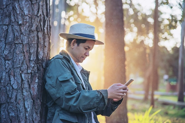Asian man with mobile phone in forest tree nature - people in spring nature and technology concept