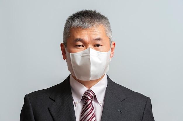 Covid19からの保護のための白い使い捨て3dフェイスマスクを身に着けているスーツとネクタイを持つアジア人男性