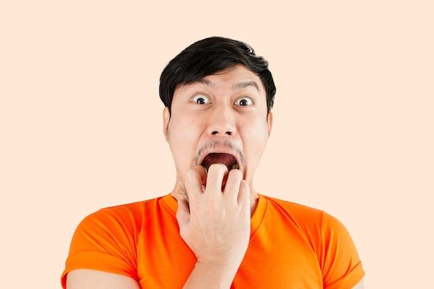 Азиатский мужчина с удивленным и шокированным лицом.