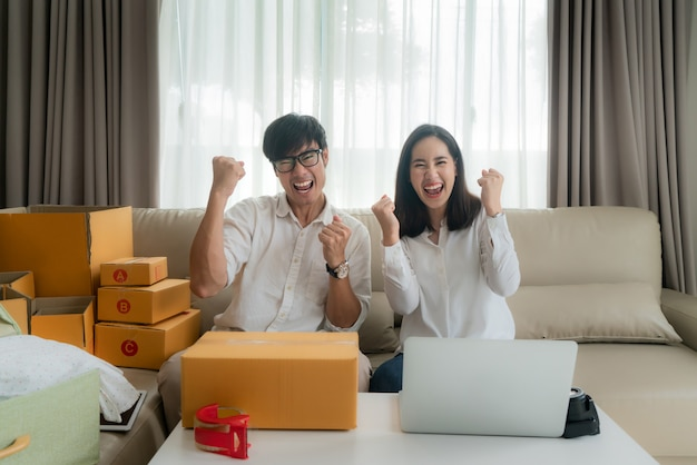 Asian man and woman are selling their online via on the computer in house and very satisfied when there are many of her orders. small business startup sme entrepreneur or freelance concept