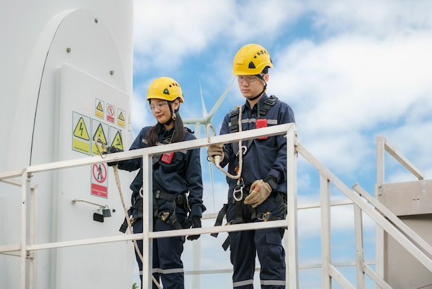 Asian man and woman inspection engineers preparing and progress check of a wind turbine with safety in wind farm in thailand.