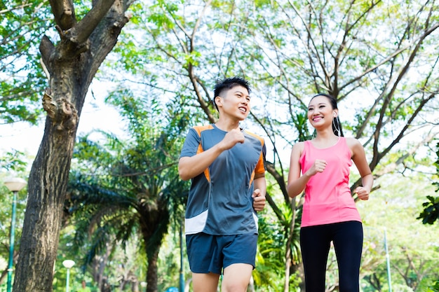 Asian man and woman jogging in city park