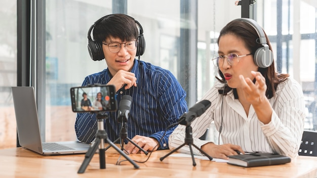Asian man and woman podcasters in headphones recording content with colleague talking to microphone and camera in broadcast studio together, communication technology and entertainment concept