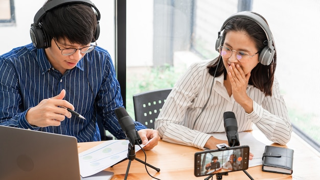 Asian man and woman podcasters in headphones recording content with colleague talking to microphone and camera in broadcast studio together