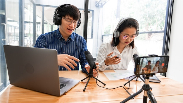 Asian man and woman podcasters in headphones recording content with colleague