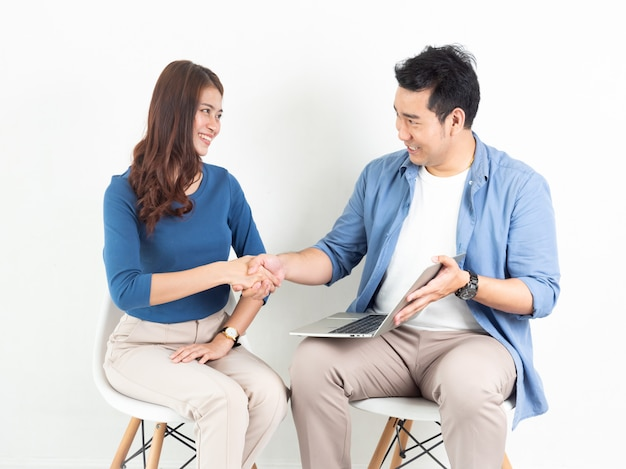 Asian man and woman talking with laptop computer for business on white background