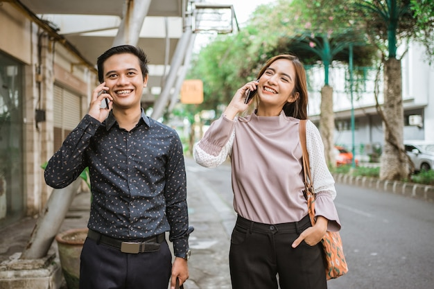 Asian man and woman on their phone talking while going to office