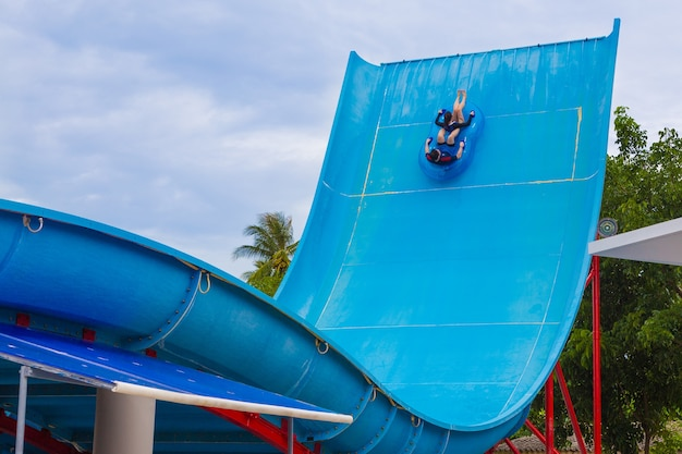 Asian man and woman tourist female slide down boomerango water slider