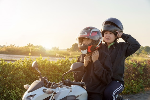 Asian man and woman with helmet and wearing and fasten before riding big bike motorcycle on the road for safety