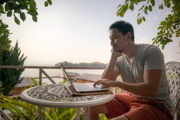 アジアの男は美しい湖の風景とカフェで彼のラップトップに取り組んでいます。