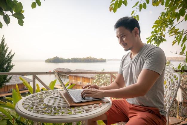 アジア人は美しい風景とカフェで彼のラップトップに取り組んでいます。
