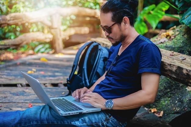 アジア人の男性が働いて、屋外の自然の中でラップトップ上で写真をチェックし、彼はリラックス