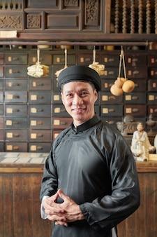古い中国の薬局で働いているアジア人