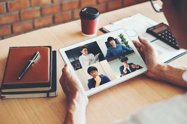 アジア人の男性が自宅で仕事をしていてビデオ通話