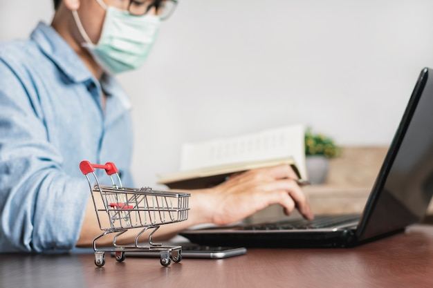 Asian man working at home office and wear a mask to protect against corona virus