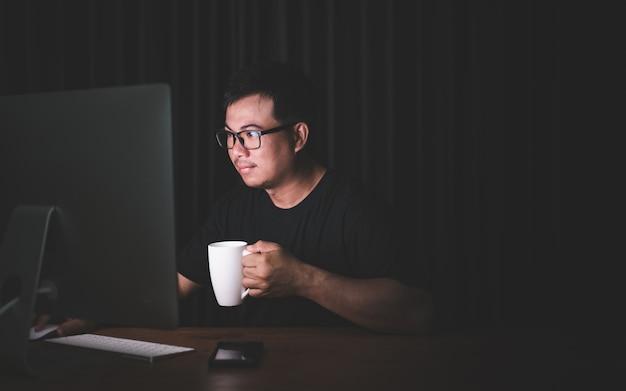 暗い部屋でコンピューターに取り組んでいて、コーヒーカップを保持しているアジア人男性