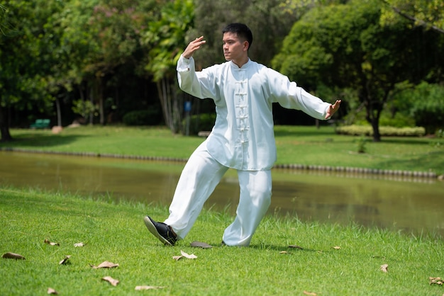 Asian man working out with tai chi in the morning at the park, chinese martial arts