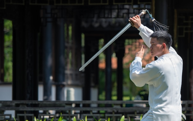 Asian man working out with tai chi sword in the morning at the park, chinese martial arts, healthy care for life concept.