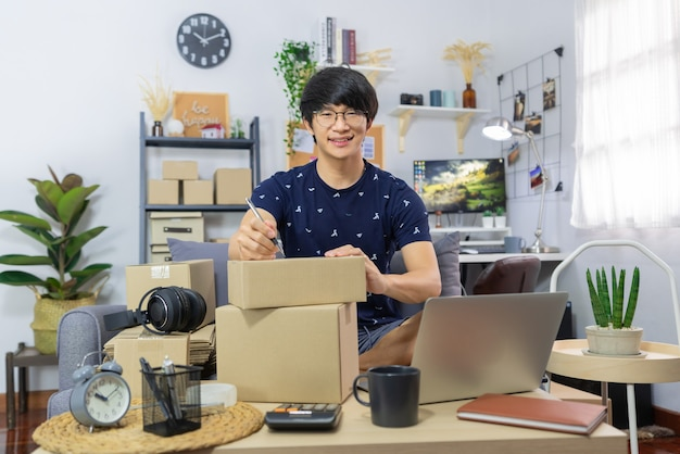 Asian man working sell online writing address on package of orders