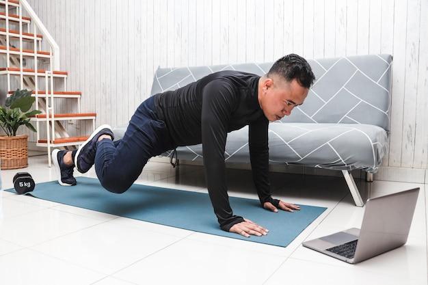Азиатский мужчина тренируется дома во время просмотра видео-урока фитнеса на ноутбуке
