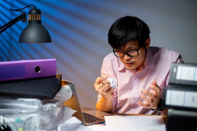 Азиатский менеджер мял бумагу после того, как не может думать о своем проекте и работе по ночам. злой тайский офисный человек сосредоточился и разочаровался сверхурочно в полночь.