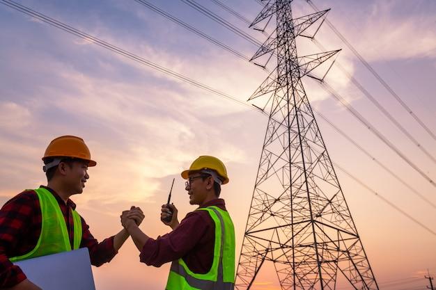 Азиатский менеджер по инженерным работникам и рабочий в стандартной форме безопасности проверяют высоковольтный столб и показывают успех после завершения работ.