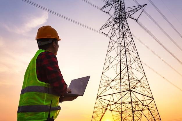 Азиатский менеджер по инжинирингу в стандартной рабочей форме безопасности проверяет высоковольтный полюс электричества.