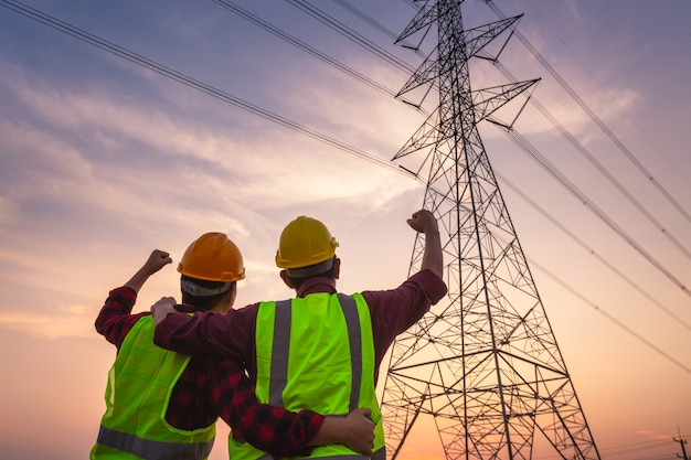 Asian manager engineering and worker in standard safety uniform working inspect the electricity high voltage pole and show success after work is completed.