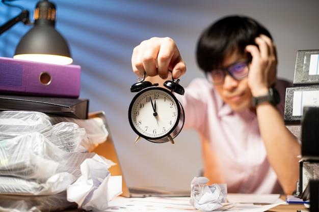 Азиатский менеджер mah держит будильник для сверхурочной работы шоу в офисе. концентрированный образ жизни подавлен сверхурочно. ночной проект на рабочем месте. депрессия занята.